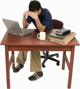 Photo of a person at a desk with head in hands.
