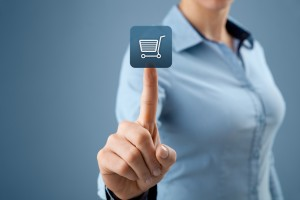 e-commerce concept photo. Woman's torso with finger pressing shopping cart button floating in front.