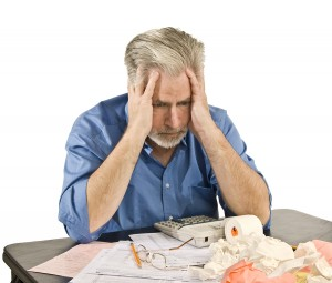 Mature man getting a headache from taxes and bills