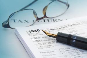Tax accounting 1040 US Tax Form, with calculator, pen and glasses